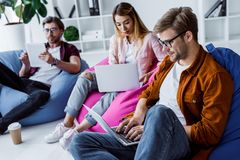 Multicultural colleagues working on startup project in office and sitting on bean. Bag chairs royalty free stock images
