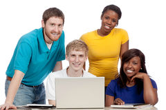 Multicultural College Students around a computer. Multicultural College students/friends, male and female, gathered around a computer stock photos