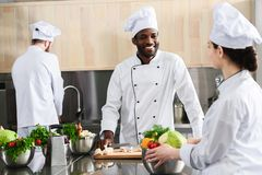 Multicultural cooks working together. By kitchen counter stock images