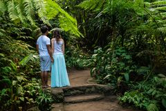 Multicultural couple holding hands on walking trail in tropical forest. Young mixed race couple on vacation in Asia. Ubud, Bali, stock image