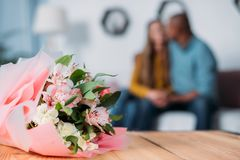 Multicultural couple kissing with bouquet. On foreground royalty free stock photos