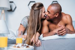 Multicultural couple kissing and lying. On bed royalty free stock image