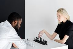 Multicultural couple playing chess near black. And white wall royalty free stock images