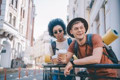 Multicultural couple of tourists holding coffee cups. And looking away stock photography