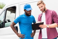 Multicultural courier and client looking at clipboard. Near van stock image