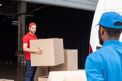 multicultural delivery men in red and blue uniform with cardboard stock photo