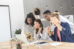 Multicultural excited business people looking at laptop screen together at workplace. In office stock photo