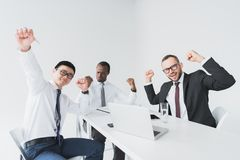 multicultural excited businessmen looking at camera while sitting at workplace royalty free stock image