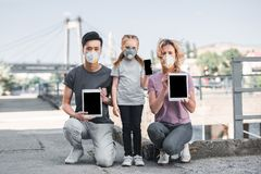Multicultural family with child in protective masks holding gadgets air. Pollution concept stock photography