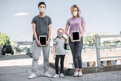Multicultural family with child in protective masks holding tablets air. Pollution concept royalty free stock photography