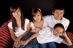 Multicultural Family Portrait. Teen children from a multicultural American family of six in a seated studio portrait with a black background stock photo