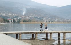 Multicultural family walks on the pier of Ohrid lake. OHRID, MACEDONIA - MARCH 12, 2017: Multicultural family walks on the pier of Ohrid lake Royalty Free Stock Images