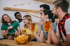 Multicultural friends with beer and chips watching soccer match and talking. At bar stock image