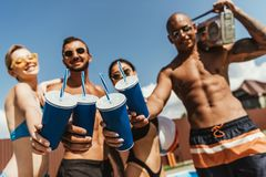 Multicultural friends with clinking cups and holding retro boombox. Selective focus royalty free stock images