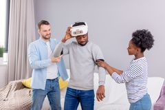 Multicultural friends help african guy to manade with vr headset for fist time royalty free stock photos