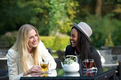 Multicultural Friends Laughing. Multicultural friends drinking and enjoying their tea outdoors Royalty Free Stock Photo