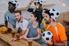 Multicultural friends in soccer ball hats celebrating gesturing by hands and watching football match. At bar royalty free stock images