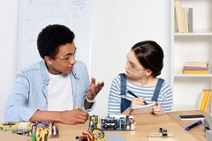 Multicultural friends studying and talking about computer motherboard. At home stock photography