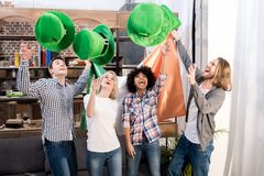 Multicultural friends throwing up green hats. On patricks day stock images