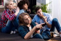 Multicultural friends watching tv with alcohol and food. At home royalty free stock image