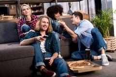Multicultural friends watching tv and eating pizza. At home stock photos