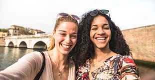 Multicultural girlfriends taking selfie having fun together - Friendship concept with happy girls at summer city vacation. Millenial lifestyle with female stock photography