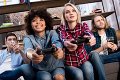 Multicultural girls playing video game on sofa at home men. Drinking beer royalty free stock photos
