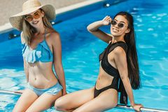 Multicultural girls in swimsuits and sunglasses sitting. At swimming pool royalty free stock photo
