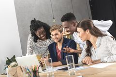 Multicultural group of business people using laptop together at workplace. In office stock photos