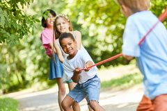 Group of children as a strong team in tug-of-war. Multicultural group Children as strong team in tug of war competition stock photography