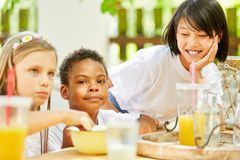 Multicultural group of children having breakfast together royalty free stock images
