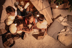 Multicultural group of children reading book together. High angle view of multicultural group of children reading book together stock image