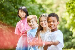 Multicultural group of children in tug of war. Multicultural group Children in tug of war as a team in nature royalty free stock images