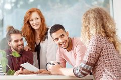 Multicultural group of co-workers. Smiling during an appointment with boss in the office royalty free stock image