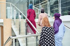 Group of four muslim girls walking at stairs of shopping mall royalty free stock photo