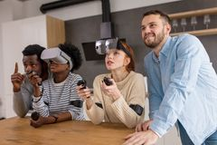 Multicultural group of friends playing games using virtual reality glasses. royalty free stock images