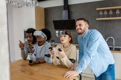 Multicultural group of friends playing games using virtual reality glasses. Virtual battle of two multiracial teams, consisting of loving african and caucasian stock photos