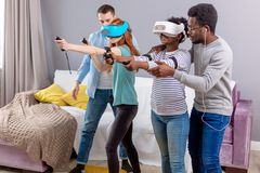 Multicultural group of friends playing games using virtual reality glasses. Virtual battle of two multiracial teams, consisting of loving african and caucasian stock photo