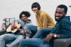 Multicultural group of friends sitting on couch and playing. Guitar royalty free stock photos