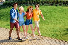 multicultural group of friends walking on street together stock image