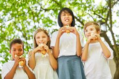 Multicultural group of kids is eating baguette. Multicultural group of kids eats baguette buns at a garden party Royalty Free Stock Photography