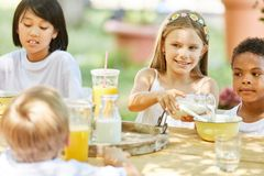 Multicultural group of kids having breakfast royalty free stock image