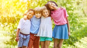 Multicultural group of kids hugs each other in summer. Happy multicultural group of kids hugs each other in summer as integration concept royalty free stock photo