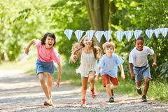 Group of kids makes a race. Multicultural group of kids makes race on the kids birthday stock photography