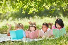 Multicultural group learning to read children. Multicultural group of children reading while studying in the park in summer Stock Image