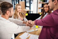 Multicultural group of marketing managers holding hands together in office. Teamwork concept royalty free stock photo