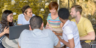 Multicultural group of people discussing by laptop. At table outdoors Royalty Free Stock Images