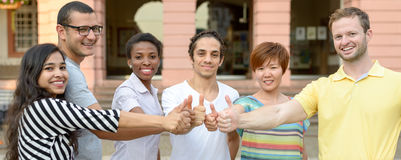 Multicultural group of students giving thumbs up stock images
