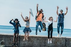 Multicultural group of young friends jumping of. Parapet together royalty free stock photography