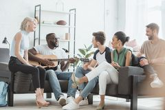 Multicultural group of young people sitting in living room and playing acoustic. Guitar royalty free stock images